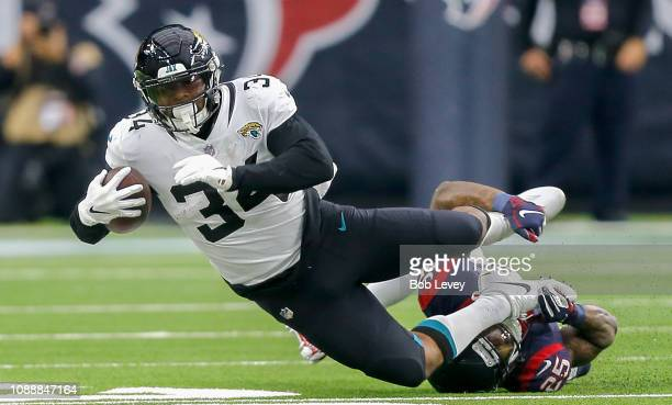 Carlos Hyde of the Jacksonville Jaguars is tackled by Kareem Jackson of the Houston Texans at NRG Stadium on December 30 2018 in Houston Texas
