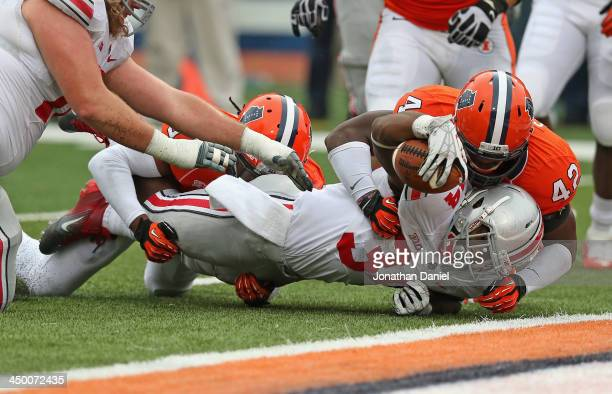 Carlos Hyde of the Ohio State Buckeyes is stopped just short of the goal line by Ralph Cooper and Earnest Thomas of the Illinois Fighting Illini at...
