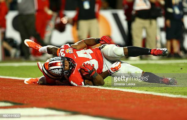 Carlos Hyde of the Ohio State Buckeyes is tackled near the goal line after a run in the third quarter against the Clemson Tigers during the Discover...