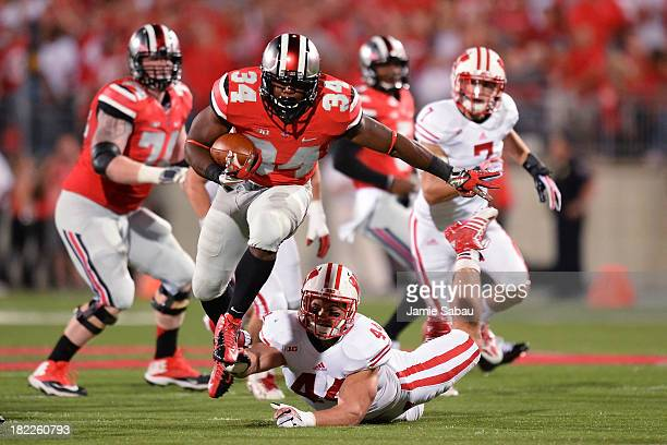 Carlos Hyde of the Ohio State Buckeyes leaps to avoid a tackle by Chris Borland of the Wisconsin Badgers in the first quarter at Ohio Stadium on...