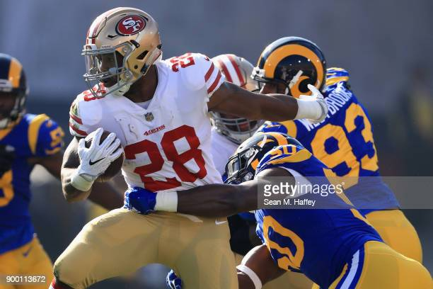 Carlos Hyde of the San Francisco 49ers breaks a tackle by Samson Ebukam of the Los Angeles Rams during the first half of a game at Los Angeles...