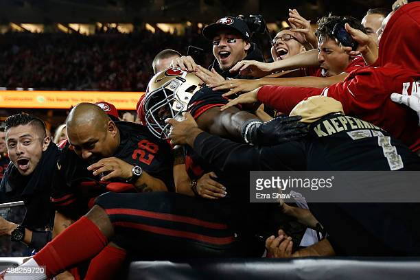 Carlos Hyde of the San Francisco 49ers celebrates his touchdown against the Minnesota Vikings by jumpin into the stands during their NFL game at...
