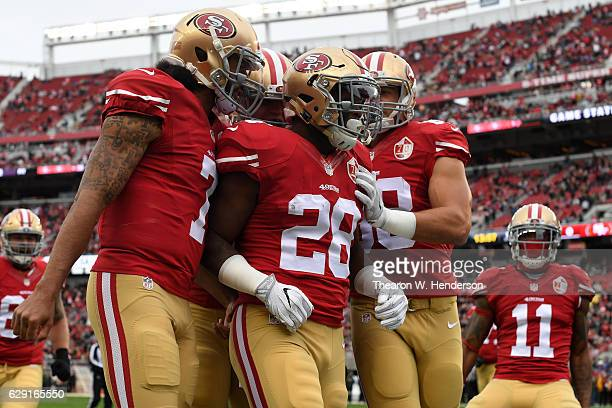 Carlos Hyde of the San Francisco 49ers celebrates with teammates after scoring against the New York Jets in the first quarter of their NFL game at...
