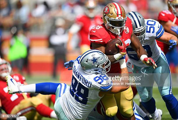 Carlos Hyde of the San Francisco 49ers gets tackled by Tyrone Crawford and Sean Lee of the Dallas Cowboys during the first half of their NFL football...