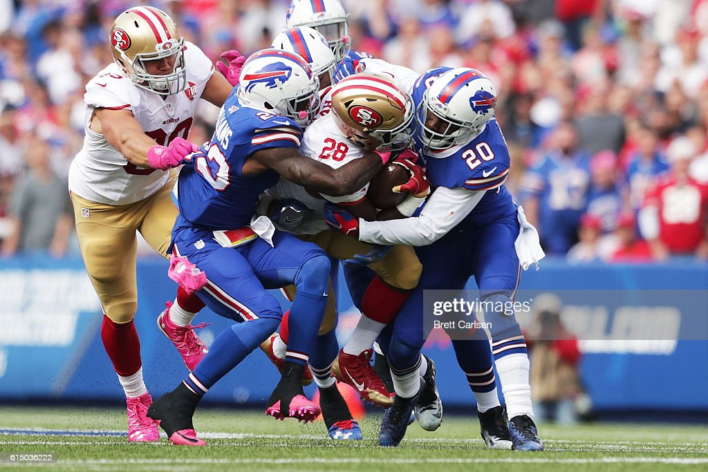 Carlos Hyde #28 of the San Francisco 49ers is hit by Aaron Williams #23 of the Buffalo Bills and Corey Graham #20 of the Buffalo Bills during the first half at New Era Field on October 16, 2016 in Buffalo, New York.
