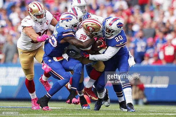 Carlos Hyde of the San Francisco 49ers is hit by Aaron Williams of the Buffalo Bills and Corey Graham of the Buffalo Bills during the first half at...
