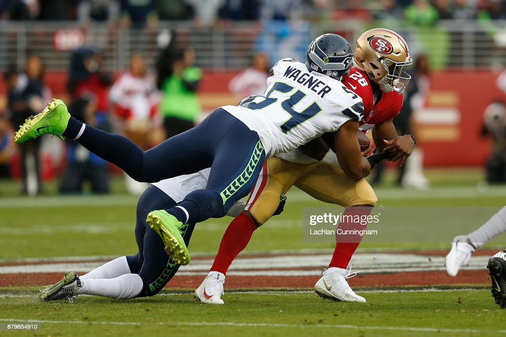 Carlos Hyde #28 of the San Francisco 49ers is tackled by Bobby Wagner #54 of the Seattle Seahawks at Levi's Stadium on November 26, 2017 in Santa Clara, California.