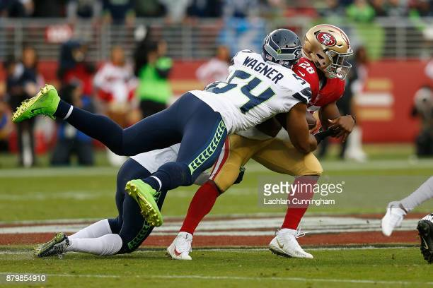 Carlos Hyde of the San Francisco 49ers is tackled by Bobby Wagner of the Seattle Seahawks at Levi's Stadium on November 26 2017 in Santa Clara...
