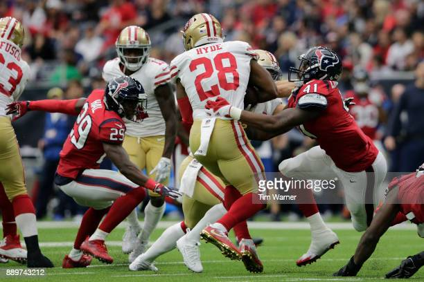 Carlos Hyde of the San Francisco 49ers is wrapped up by Zach Cunningham of the Houston Texans in the first half at NRG Stadium on December 10, 2017...