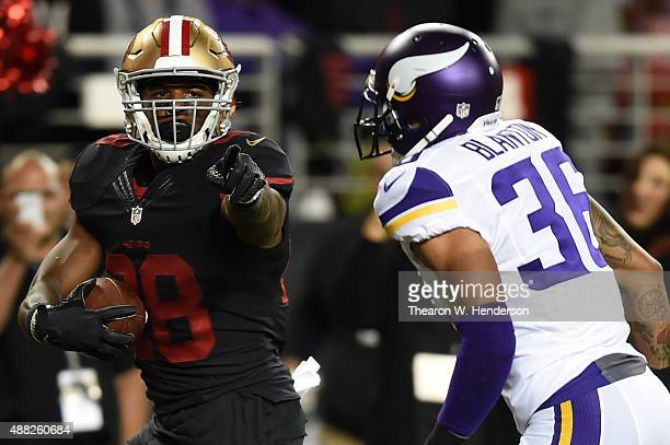 Carlos Hyde of the San Francisco 49ers points at Robert Blanton of the Minnesota Vikings as he runs for a touchdown during their NFL game at Levi's...