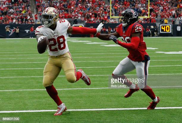 Carlos Hyde of the San Francisco 49ers scores in the second quarter as he beats Andre Hal of the Houston Texans to the endzone at NRG Stadium on...