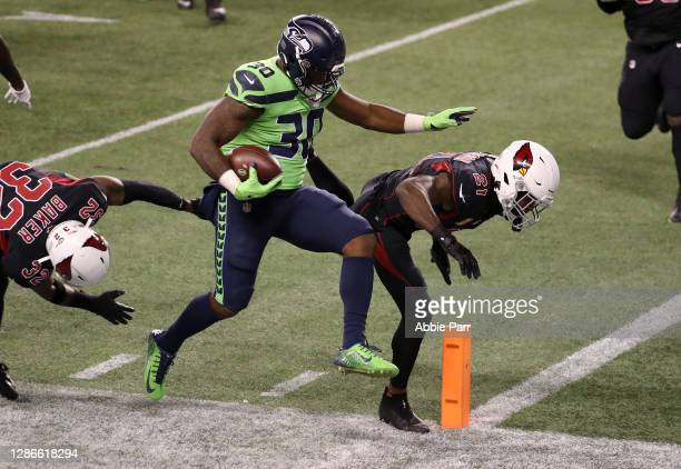 Carlos Hyde of the Seattle Seahawks is knocked out of bounds by Budda Baker and Patrick Peterson of the Arizona Cardinals at Lumen Field on November...