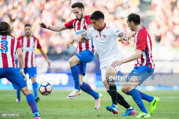 Carlos Joaquin Correa of Sevilla FC battles for the ball with Saul Niguez Esclapez and Diego Roberto Godin Leal of Atletico de Madrid during their La...