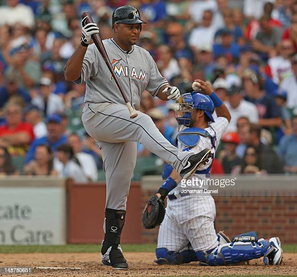 Carlos Lee of the Miami Marlins reacts after swinging and missing a pitch in the 9th inning as Geovany Soto of the Chicago Cubs throws the ball back...