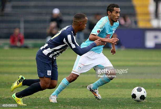 Carlos Lobaton of Sporting Cristal drives the ball as Luis Trujillo of Alianza Lima tries to stop him during a match between Alianza Lima and...