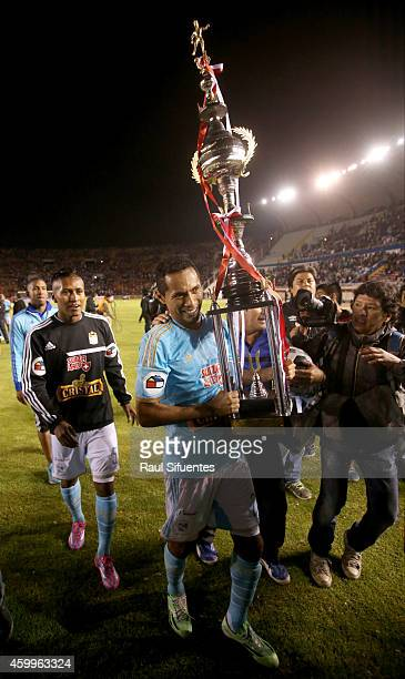 Carlos Lobaton of Sporting Cristal lifts the trophy after winning a final match between Alianza Lima and Sporting Cristal as part of Torneo Clausura...