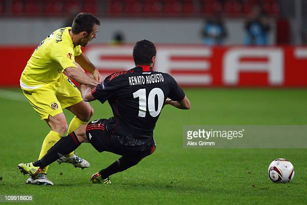 Carlos Marchena of Villarreal is challenged by Renato Augusto of Leverkusen during the UEFA Europa League round of 16 first leg match between Bayer...