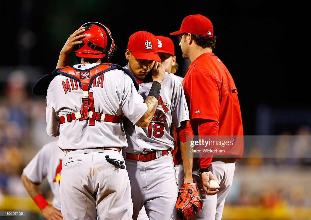 Carlos Martinez #18 of the St Louis Cardinals is hugged by teammate Yadier Molina #4 after being pulled from the game in the 8th inning by manager Mike Matheny #26 against the Pittsburgh Pirates during the game at PNC Park on July 9, 2015 in Pittsburgh, Pennsylvania.