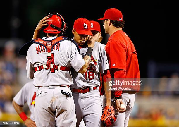 Carlos Martinez of the St Louis Cardinals is hugged by teammate Yadier Molina after being pulled from the game in the 8th inning by manager Mike...
