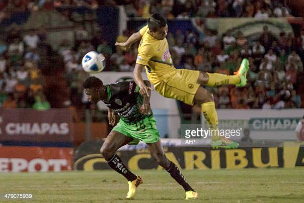 Carlos Medina of America vies for the ball with Aviles Hurtado of Jaguares during their Mexican Clausura 2014 tournament football in Tuxtla Gutierrez...