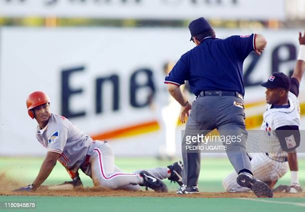 Carlos Mendoza of the Venezuela's Cardenales de Lara looks back at second base umpire Michael Pilato as the shortstop for the Tigres of Licey of the...