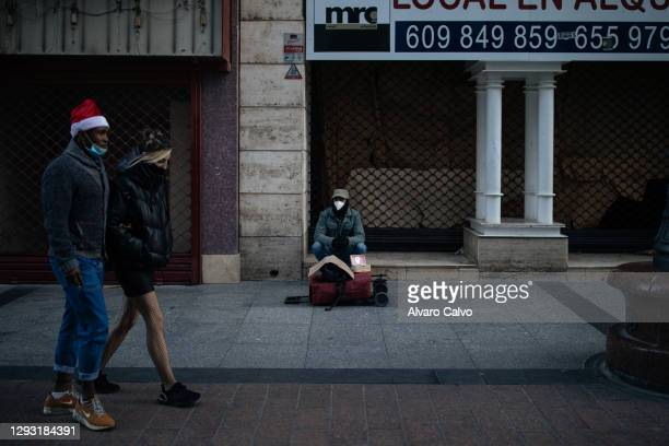 """Carlos Miguel Moreira sitting in the streets of the centre of Zaragoza looking for donations and charity with a sign that says """"Please help me to..."""