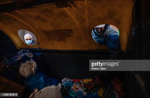 Carlos Miguel Moreira, wearing a Covid-19 protective mask, looks for food, scrap metal and abandoned objects in the rubbish containers, while other...