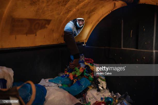 Carlos Miguel Moreira, wearing a protective mask from Covid-19, looks for food, scrap metal and abandoned objects in rubbish containers on December...