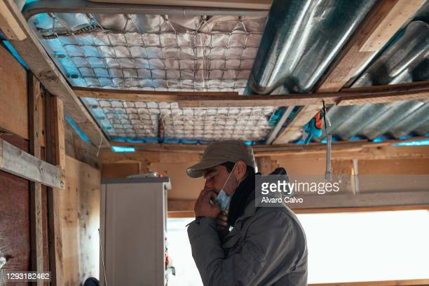 Carlos Miguel Moreira, wearing a protective mask of Covid-19, in his wooden and cardboard house located in an industrial park prepares to go out to...