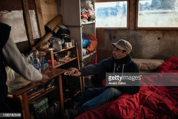 Carlos Miguel Moreira with his friend José in their wood and cardboard house located in an industrial park on December 25, 2020 in Zaragoza, Spain. A...