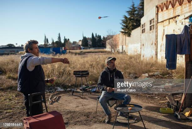Carlos Miguel Moreira with his friend José play darts at their wood and cardboard house located in an industrial park on December 25, 2020 in...