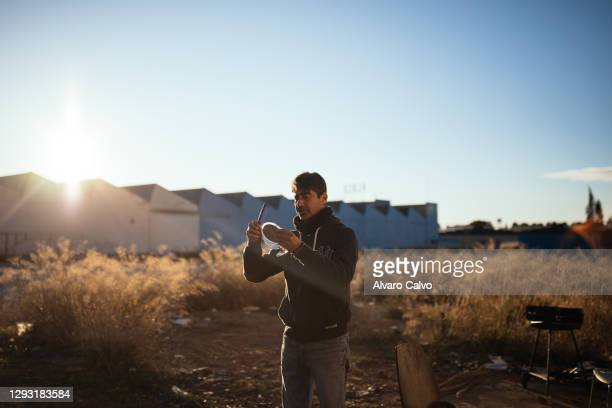 Carlos Miguel Moreirra uses a comb near his wooden and cardboard house located in an industrial park on December 25, 2020 in Zaragoza, Spain. A new...