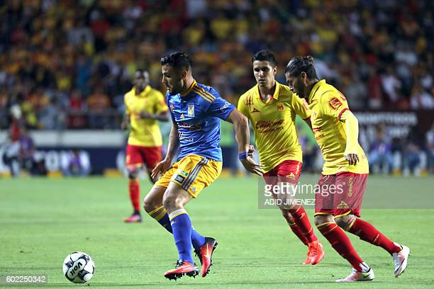 Carlos Morales and David Cabrera of Morelia vies for the ball with Jose Rivas of Tigres during their Mexican Apertura 2016 tournament football match...