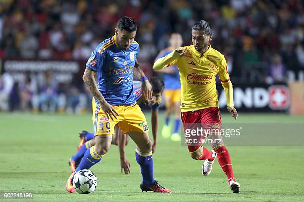 Carlos Morales of Morelia vies for the ball with Andy Delort of Tigres during their Mexican Apertura 2016 tournament football match at the Jose Maria...
