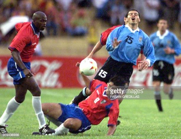 Carlos Morales of Uruguay collides with Mauricio Solis of Costa Rica as Jervis Drummond looks on 22 July 2001 at the Centenario stadium in Armenia...