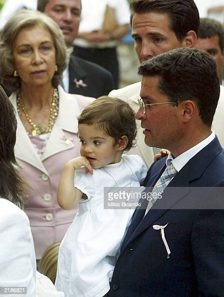 Carlos Morales Quintana holds his daughter Arrietta with is Crown Prince Pvlos one of the godfathers of the baby and Queen Sofia of Spain after...