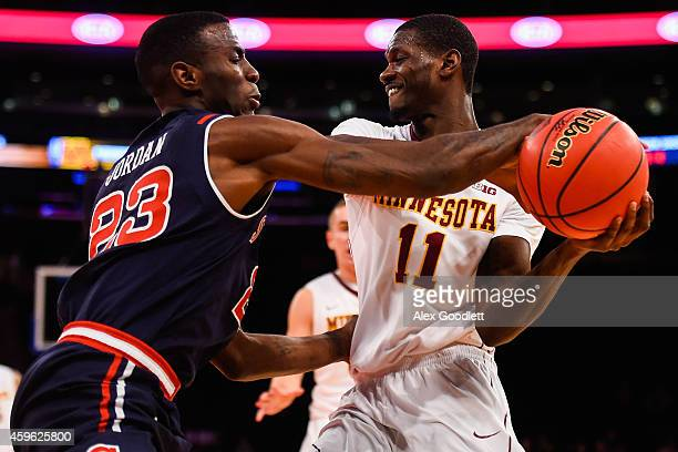 Carlos Morris of the Minnesota Golden Gophers fights for the ball with Rysheed Jordan of the St John's Red Storm in the first half at Madison Square...