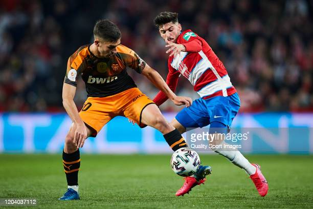 Carlos Neva of Granada CF competes for the ball with Ferran Torres of Valencia CF during the Copa del Rey quarter final match between Granada CF and...