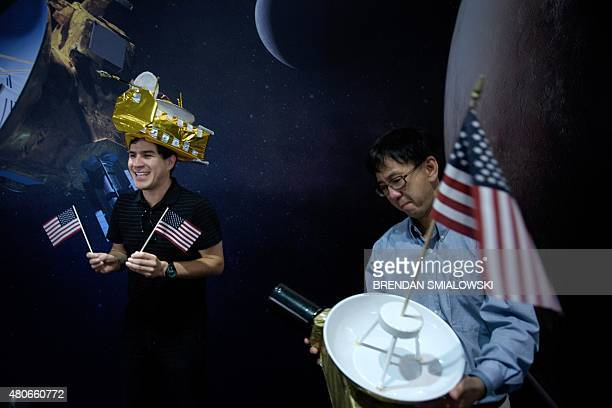Carlos Nieto and Nam Phamdo pose with New Horizons probe hats at the Johns Hopkins University Applied Physics Laboratory July 14 2015 in Laurel...