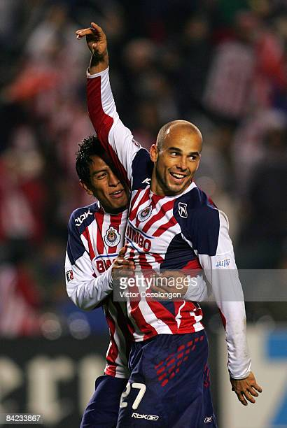 Carlos Ochoa of CD Chivas de Guadalajara celebrates his second goal of the game against Tigres UANL with teammate Omar Esparza in the second half of...