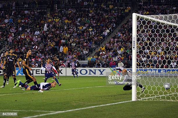 Carlos Ochoa of CD Chivas de Guadalajara watches from his stomach after heading in the ball for a goal in the first half past goalkeeper Oscar Perez...