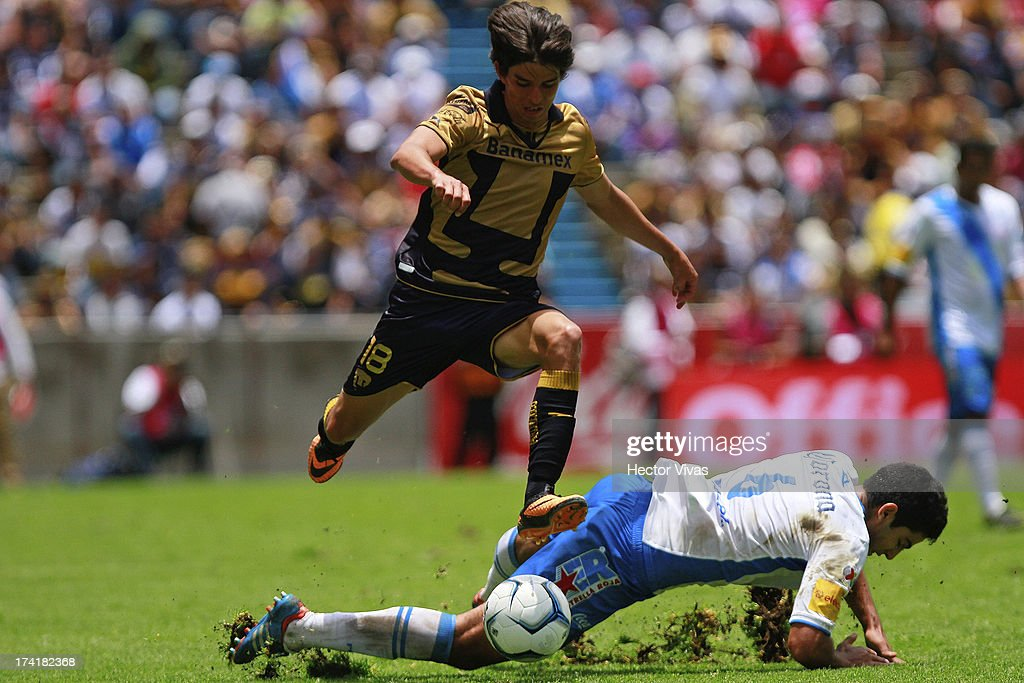 Carlos Orrantia (L) of Pumas struggles for the ball with Diego de Buen (R) of Puebla during a match between Pumas and Puebla as part of the Torneo Apertura 2013 Liga Mx at Cuauhtemoc Stadium on July 21, 2013 in Puebla, Mexico.