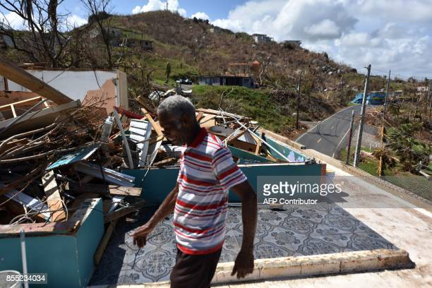 Carlos Pagan walks in his destroyed house by Hurricane Maria in Yabucoa in the east of Puerto Rico on September 28 2017 The US island territory...