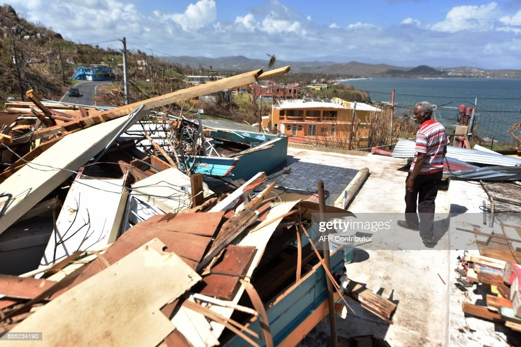 Carlos Pagan walks in his destroyed house by Hurricane Maria in Yabucoa, in the east of Puerto Rico, on September 28, 2017. The US island territory, working without electricity, is struggling to dig out and clean up from its disastrous brush with hurricane Maria, blamed for at least 33 deaths across the Caribbean. /