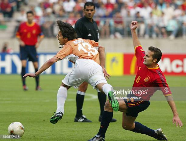 Carlos Paredes of Paraguay is tackled by Ruben Baraja of Spain during the FIFA World Cup Korea/Japan Group B match between Spain and Paraguay at the...