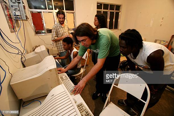 Carlos Paulino, center shows rap musician K2, right, how to use music editing software at a Linux multimedia workstation in an apartment which serves...