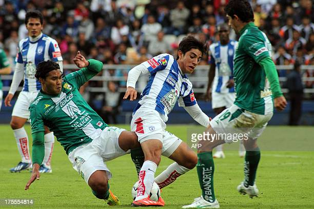 Carlos Pena and Rodolfo Pizarro of Pachuca vie for the ball with Jose Magallon of Leon during their tournament Apertura 2013 of Mexican League in...