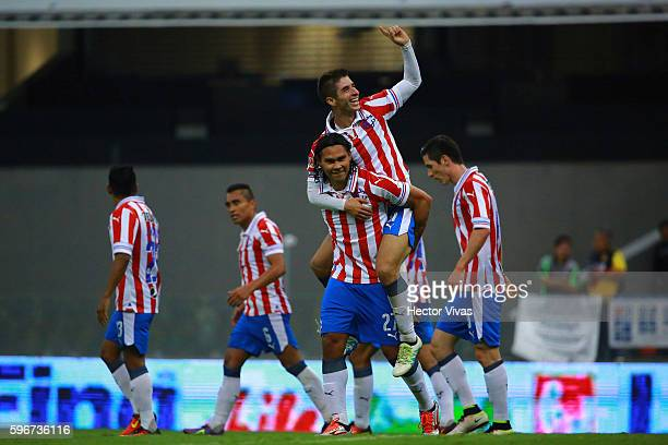 Carlos Pena of Chivas celebrates with teammates after scoring the third goal of his team during the 7th round match between America and Chivas as...