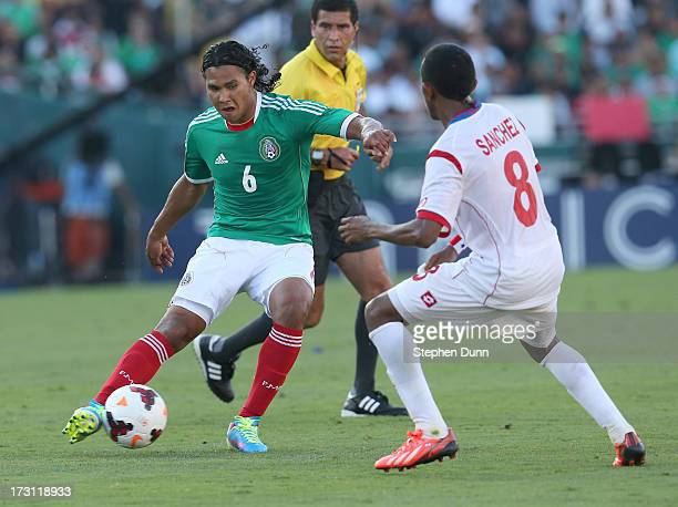 Carlos Pena of Mexico controls the ball against Marcos Sanchez of Panama during the first round of the 2013 CONCACAF Gold Cup at the Rose Bowl on...