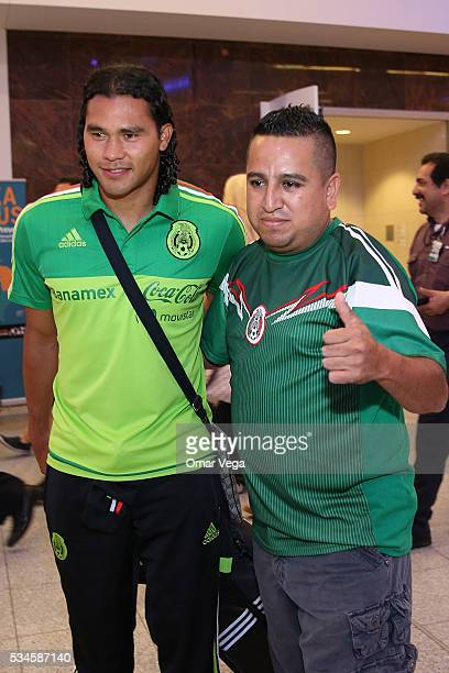 Carlos Pena of Mexico poses for photos with a fan during the Mexico National Team arrival to United States at HartsfieldJackson International Airport...